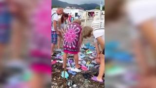 В Сочи на пляже туристы бросились разбирать выброшенную штормом на берег обувь