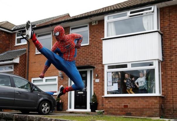 Мужчина в костюме человека-паука поднимает настроение детям, сидящим на карантине в Стокпорте, Великобритания